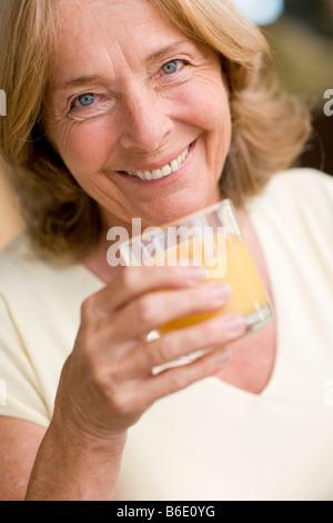 O-Saft trinken. Frau mittleren Alters mit einem Glas Orangensaft in der Hand. - Stockfoto