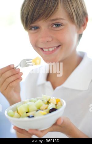 Gesunde Ernährung. 10 Jahre alter Junge einen Obstsalat zu essen. - Stockfoto
