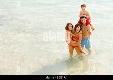 Familie im Urlaub stehen im Meer. - Stockfoto