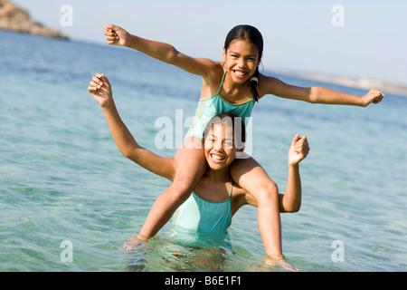 Schwestern im Urlaub. Mädchen sitzen auf ihrer Schwester Schultern im Meer. - Stockfoto