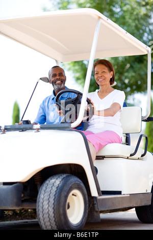 Golf-Spieler. Mann und Frau mit einem Golfwagen während einer Runde Golf. - Stockfoto