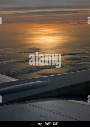 Untergehende Sonne über dem Meer aus Flugzeug-Fenster - Stockfoto