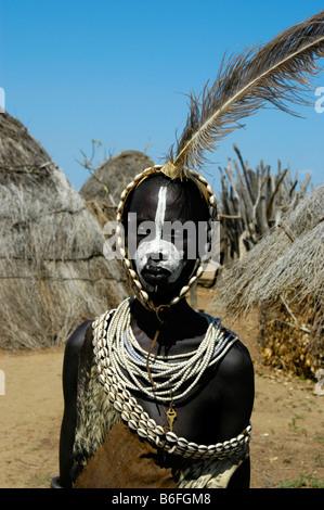 Young-Karo Stammesangehörige tragen Federn in einem Stirnband und Halsketten von Kauri-Muscheln stehen zwischen - Stockfoto