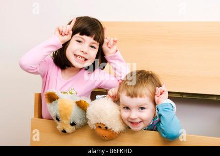 Zwei Schwestern, 6 und 3 Jahre alt, mit Eselsohren, Brünette und Blonde, drinnen - Stockfoto