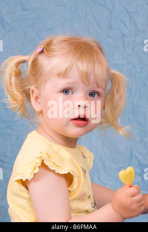 Blonde Mädchen, 2 Jahre, mit lollipop - Stockfoto