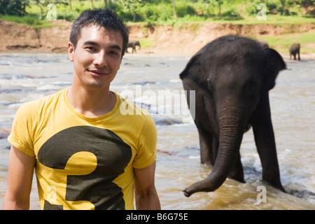 Ein Tourist, posiert für ein Foto vor einem Elefanten am Maha Oya Fluss in der Nähe von The Pinnawela-Elefantenwaisenhaus - Stockfoto