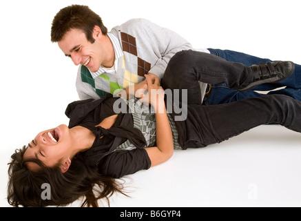 Ein junges Mädchen wird von einem jungen Mann gekitzelt. - Stockfoto