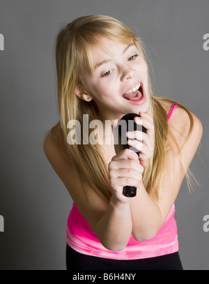 Kind in ein Mikrofon singen - Stockfoto