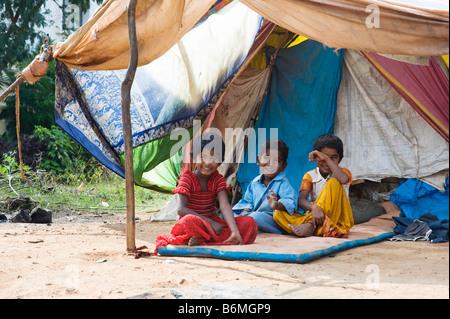 Glückliche armen indischen Kinder sitzen vor ihrem Zelt nach Hause. Andhra Pradesh, Indien - Stockfoto
