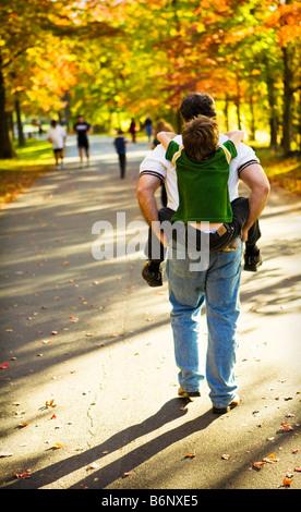 Vater & Sohn Piggy Back Fahrt an einem Herbsttag in der herbstlichen Farben des Waldes - Stockfoto