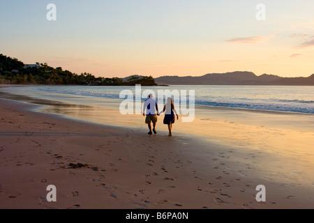 Paar genießt zu Fuß am Strand entlang zum Sonnenuntergang entlang Flamingo Beach in Costa Rica - Stockfoto