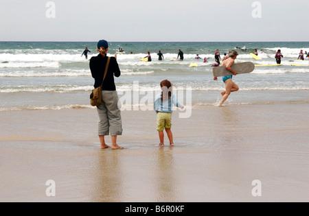 Mutter und Tochter gerade Menschen Surfen und Schwimmen am Polzeath sandigen Strand in Cornwall - Stockfoto