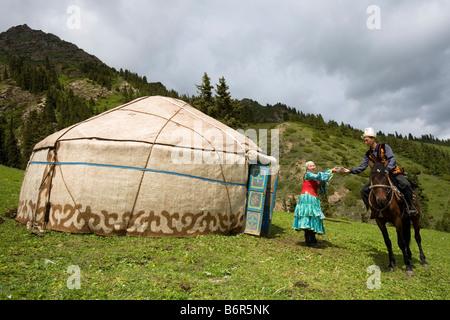 Kirgisischen Mann Tracht Empfang willkommen Tee von seiner Frau nach seiner Rückkehr aus seinem Vieh hüten. - Stockfoto