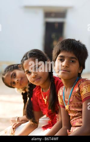 Drei junge Indianerdorf Mädchen sitzen auf einer Bank in einem ländlichen Dorf. Andhra Pradesh, Indien. Selektiven - Stockfoto
