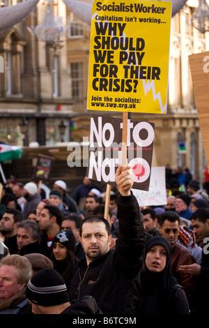 Ein Mann hält ein Plakat während einer Demonstration unter Grays Monument in Newcastle, England. - Stockfoto
