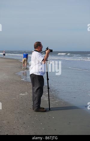 Im mittleren Alter übergewichtig Fotograf bereitet sich auf Bilder von den Atlantischen Ozean zu nehmen.  Foto von - Stockfoto