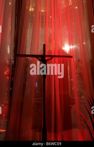 Eine Statue von Jesus am Kreuz gegen einen roten Vorhang in einer Kirche