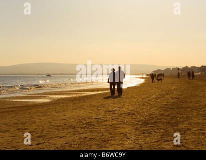 Ein paar Spaziergang bei Sonnenuntergang am Strand von Bournemouth. Dorset. VEREINIGTES KÖNIGREICH. - Stockfoto