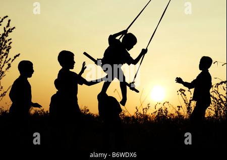 Silhouette der indischen Kinder spielen auf einem hausgemachten Schaukel in der Landschaft bei Sonnenuntergang. - Stockfoto