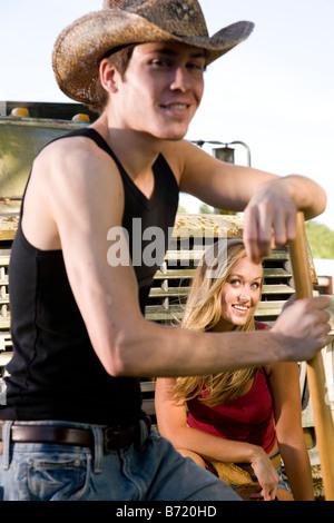 Junges Paar mit Cowboy-Hut vor alten LKW, Frau im Fokus - Stockfoto