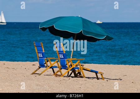 Szene von zwei blauen Liegestühle & dunkel grün Sonnenschirm auf Sand am Strand mit tiefblauem Meer & Himmel & Sonne - Stockfoto