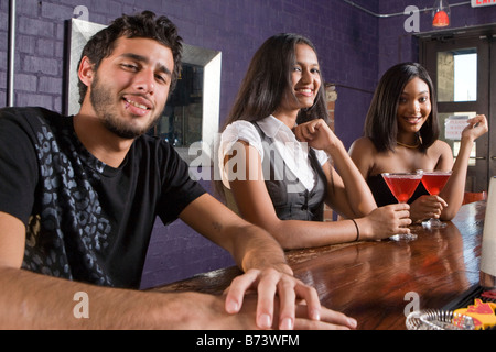 Multi-ethnischen Freundinnen trinken und flirten mit den Jüngling am Restaurantbar - Stockfoto