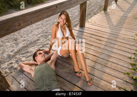 Junges Paar am Holzsteg über Sand entspannen - Stockfoto