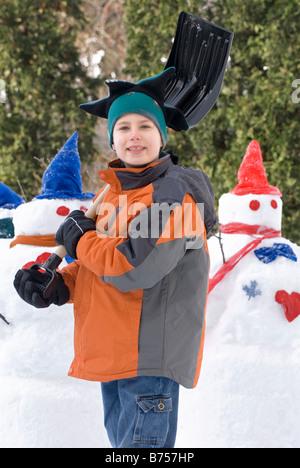 Zehn Jahre alter Junge mit Schaufel neben Schneemänner, Winnipeg, Kanada - Stockfoto