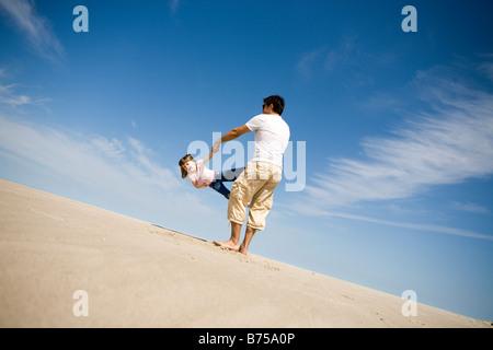 Man schwingt Mädchen (4) im Kreis, Grand Beach Provincial Park, Manitoba, Kanada - Stockfoto