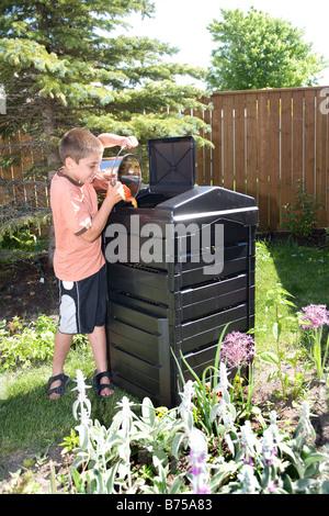 Junge mit Kompost-Eimer neben Komposter im Hinterhof, Winnipeg, Manitoba, Kanada - Stockfoto