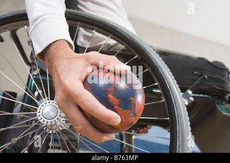 Nahaufnahme eines behinderten Mannes Hand hält eine Bowling-Kugel - Stockfoto