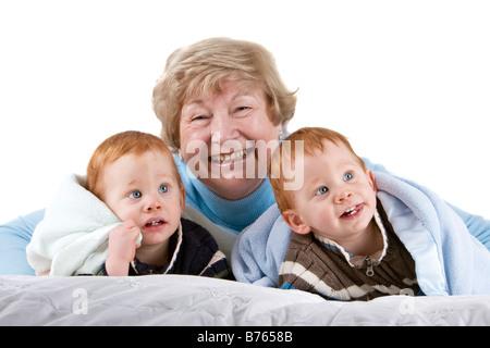Glückliche Großmutter mit Rothaarige Enkel mit Decke - Stockfoto