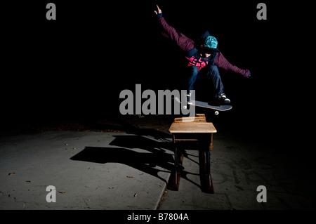 Skateboarder springen über Schreibtische - Stockfoto