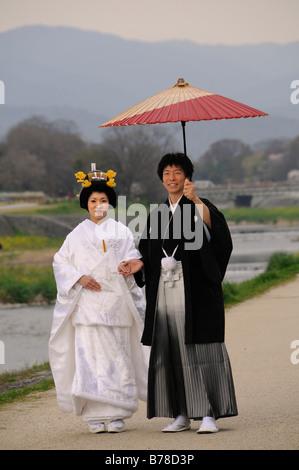 Traditionelle japanische Hochzeitspaar tragen Kimonos, Braut mit Hochzeitsfrisur, pflegen einen traditionellen Papier - Stockfoto