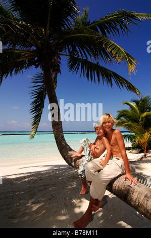 Kinder auf einem Palm-Baumstamm in Kurumba Resort, Malediven, Indischer Ozean - Stockfoto