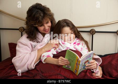 Mutter und Tochter ein Geschichtebuch im Bett lesen - Stockfoto