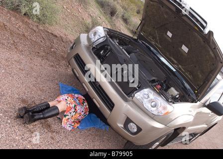 Eine Frau geht es um ihr kaputtes Auto auf einem abgelegenen Feldweg - Stockfoto