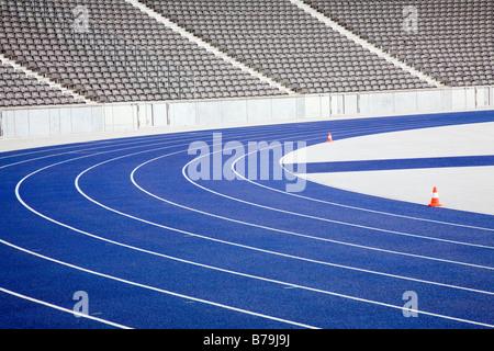 Laufstrecke im leeren Stadion blauen Hintergrund der leeren Sitzreihen verfolgen - Stockfoto