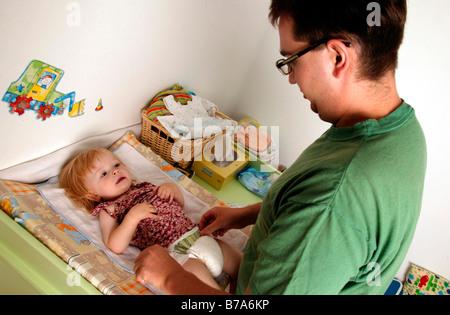 Der Vaters verändert ein Baby Windel - Stockfoto