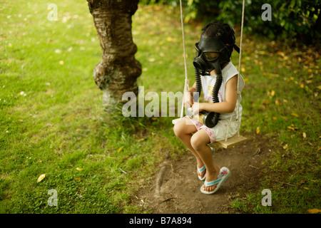 Fünf Jahre altes Mädchen auf Schaukel mit einer Gasmaske sitzt