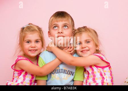 3 jährige Zwillingsmädchen umarmen einen sieben Jahre alten junge - Stockfoto