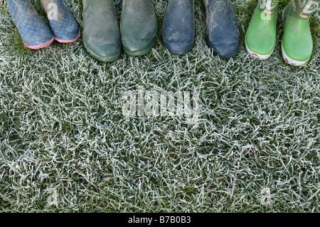 eine Aufstellung einer Familie von Wellington Stiefel links auf einige frostigen grünen Rasen zeigt nur die Zehen - Stockfoto