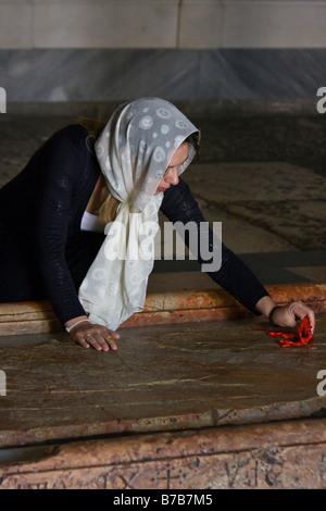 Christian Woman wischte sich die Stein der Salbung in der Kirche des Heiligen Grabes in Jerusalem - Stockfoto