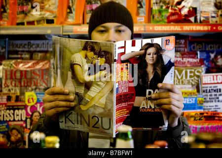 Ein Mann liest eine Zeitschrift FHM - Stockfoto