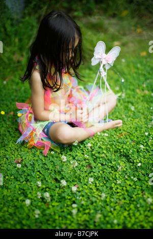 Fünf Jahre altes Mädchen im Garten in ihr Spiel Kleidung gekleidet - Stockfoto