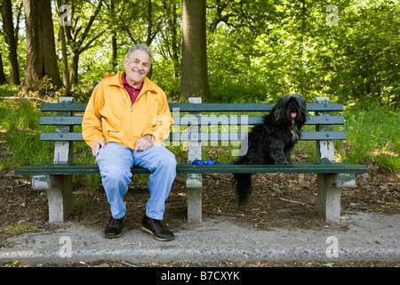 Ein Mann sitzt mit seinem Hund auf einem Park Bench, Prospect Park, Brooklyn, New York, USA - Stockfoto