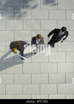 Drei Geschäftsleute zu Fuß mit einem Schutzhelm und blueprint - Stockfoto