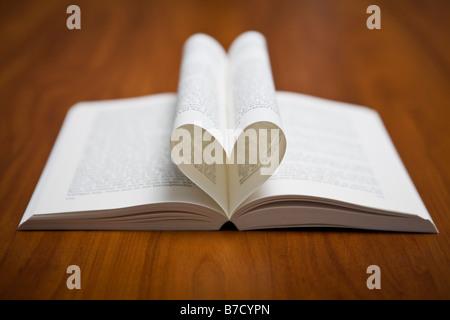 Seiten eines Buches in Form eines Herzens gefaltet - Stockfoto