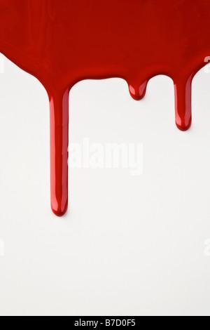 Rote Farbe tropfte eine weiße Wand - Stockfoto