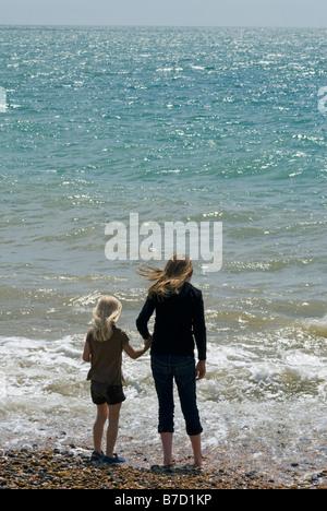 Zwei Mädchen, Paddeln im Meer am Strand von Brighton - Stockfoto